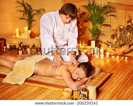Therapist man giving Thai stretching massage to woman. - stock photo