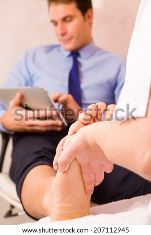 Therapist massaging businessman's foot - stock photo