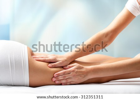 Therapist massaging upper back part of female leg. Hands applying pressure on hamstrings. - stock photo