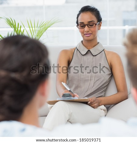 Therapist talking with couple on the couch and taking notes in therapists office - stock photo
