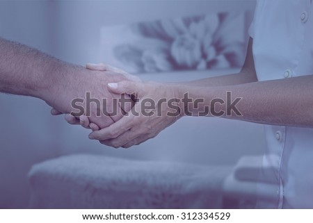 Therapist welcoming new patient - Female therapist holding hand of male client greeting him into therapy room with muted cool colors and soft focus background