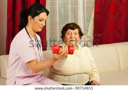 Therapist woman helping senior to do exercises with barbell home - stock photo