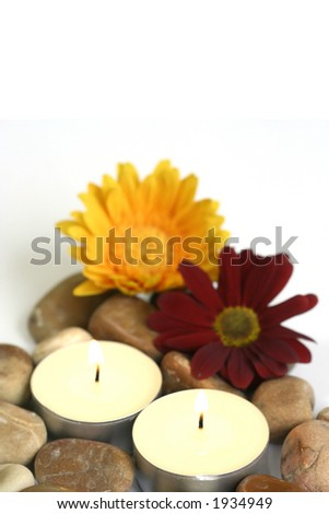 Therapy stones and fresh chrysanthemums with lighted candles suitable for spa setting and relaxation therapy, isolated on white with copyspace - stock photo
