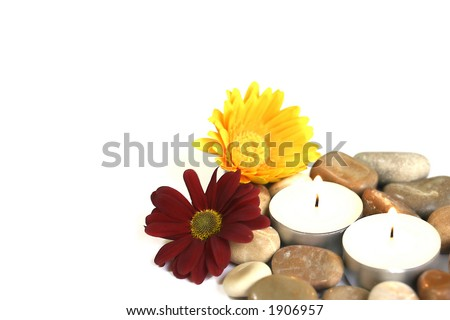 Therapy stones with a yellow and red chrysanthemum each and burning candles. Suitable for a health farm and beauty spa. With copyspace. - stock photo
