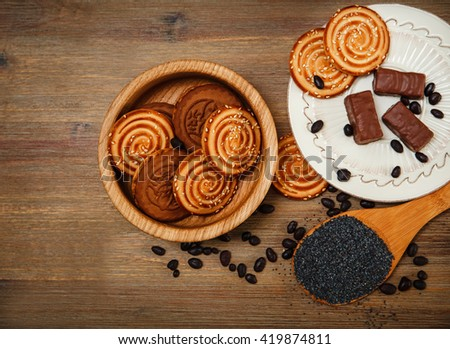There are Cookies,Candy,Chocolate Peas,Poppy;Porcelain Saucer,Tasty Sweet Food on the Wooden Background,Top View - stock photo