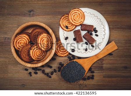 There are Cookies,Candy,Chocolate Peas,Poppy;Porcelain Saucer,Tasty Sweet Food on the Wooden Background,Top View,Toned - stock photo