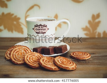 There are Cookies,Chocolate Candy, Porcelain Saucer and Cap with Coffe,Tasty Sweet Food on the Wooden Background,Toned - stock photo