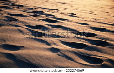 There are many footsteps on the sandy slope at sunset. These tracks are smoothed with wind.  - stock photo