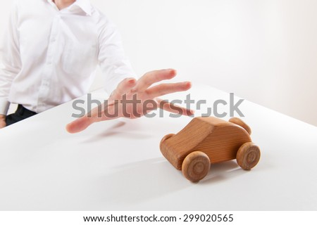 There is a car model on a white table, businessman description
