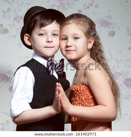There is a portrait of the smiling girl and boy on the floral background. Studio photo - stock photo