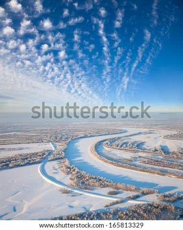 There is aerial view of countryside road which is near forest river during cold winter day. Magnificent hoarfrost is on trees.  A winter forest is in a hard frost. - stock photo
