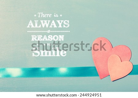 There is always a reason to smile text with pink paper hearts on blue wooden board - stock photo