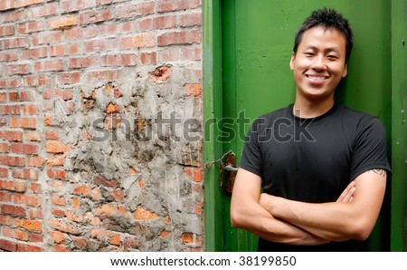 There is an Asian man stand against a old door and smile. - stock photo