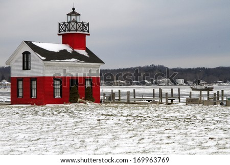 There is little activity at the Kalamazoo River Lighthouse. An old tug boat sits stranded in the icy river during the early part of winter. Saugatuck, Michigan, USA. - stock photo