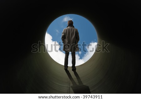 There is no other way out. Man stands silhouetted at the end of tube before a bright sky. - stock photo