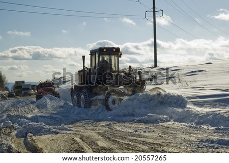 There is traffic jam from snow storm. Road technician is cleaning road - stock photo