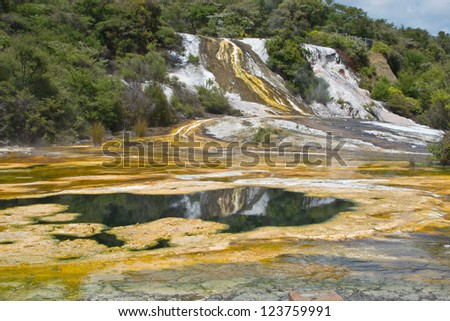 Thermal attraction in New Zealand showing silica overflows and algae in pools - stock photo