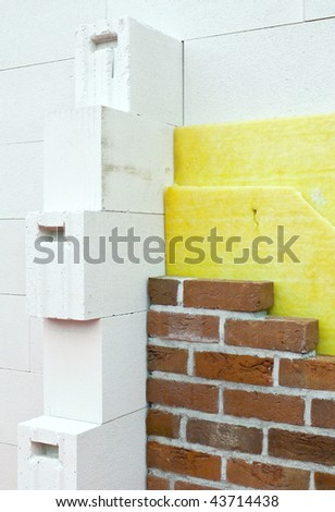 Thermal insulation of a brick wall at a construction site - stock photo