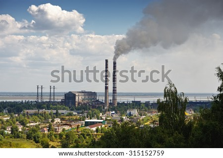 Thermal power plant with smoking chimneys on the river / ecology - stock photo