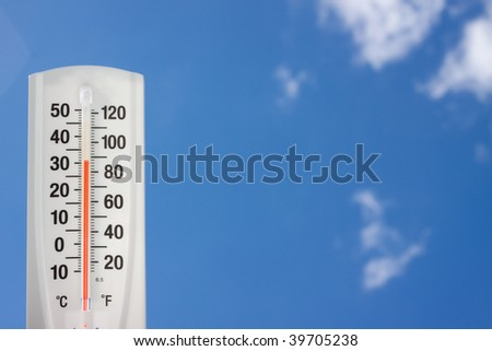Thermometer against blue sky - stock photo
