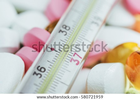 Thermometer and different colored types of pills. Medical health or drugs concept.