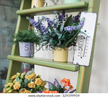 thermometer and flowers on wooden stairs