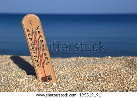 Thermometer on a beach shows high temperatures - stock photo