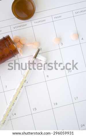 thermometer on pills with schedule background