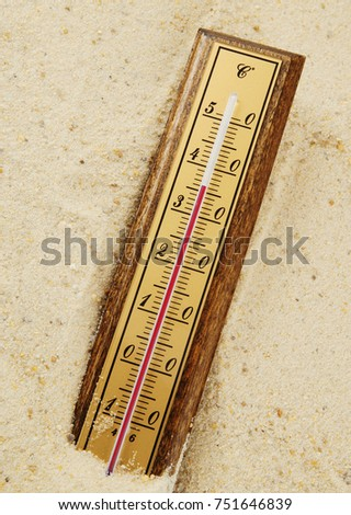 Thermometer on sand background