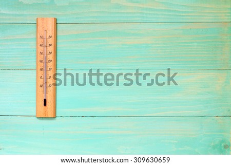 Thermometer on the wooden wall showing high temperature near 30 degrees - stock photo