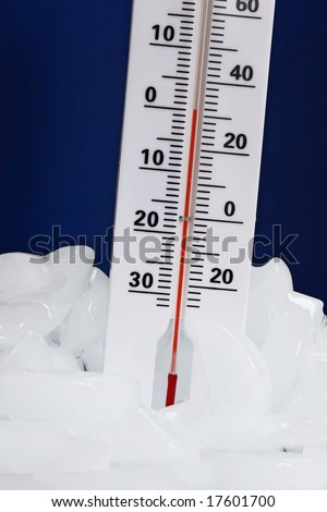Thermometer standing in melting ice against blue background, measuring ice cold temperature - stock photo