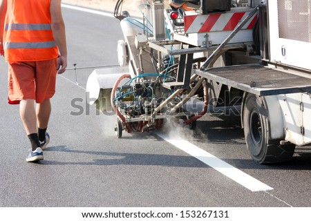 Thermoplastic spray marking machine during road construction works - stock photo