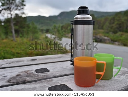Thermos and two plastic cups on the table - Close-up Photo - stock photo