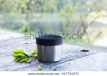 Thermos  cup of coffee on wooden table with nature on background. Tourism and travel - stock photo