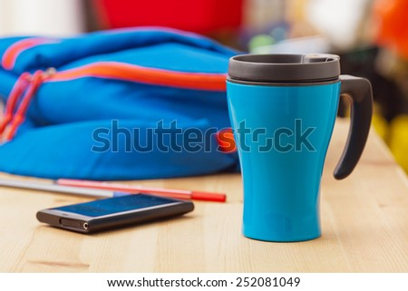 Thermos cup, smart phone and sports bag on wooden table. A healthy lifestyle concept. - stock photo