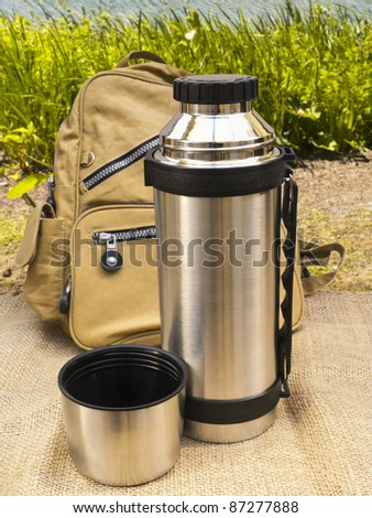 Thermos flask on burlap with backpack against nature background - stock photo