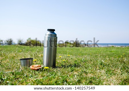 Thermos with bread on a grass field at the coast in springtime. - stock photo