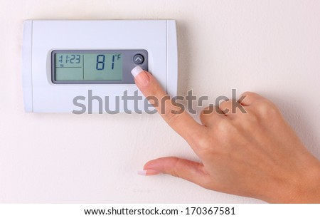thermostat. woman's hand setting the room temperature on a modern programmable wall heater. closeup - stock photo