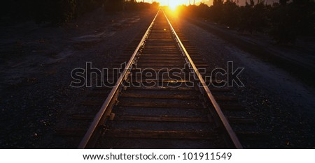 These are railroad tracks that go off into infinity at sunrise. The sun is at the end of the tracks at the horizon. - stock photo