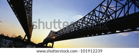 These are the Twin Bridges that lead into New Orleans. They are over the Mississippi River at sunset. - stock photo