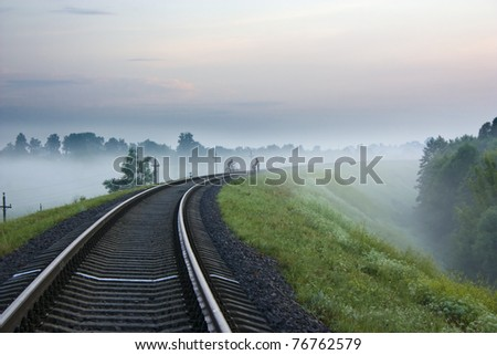 These are two cyclists cross the railway, in the early morning mist. - stock photo