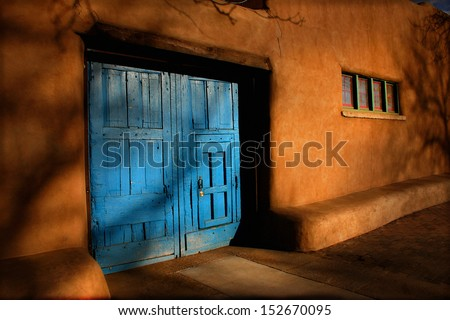 These heavy, bright blue wooden doors, are offset by the rich, warm tones of sunrise on the Adobe walls of this Santa Fe, New Mexico structure. Strong lighting and shadows adds mystery to this scene. - stock photo