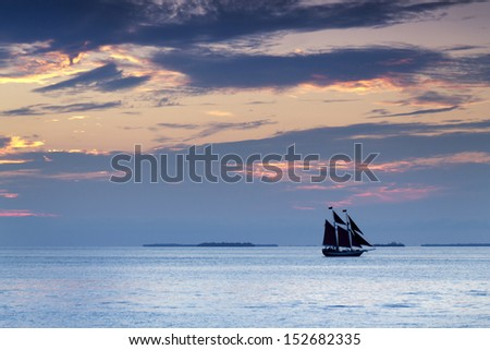 These sail boats take quiet advantage of the beautiful sunsets in Key West Florida during a sunset cruise. The colors in the sky and ocean abound. - stock photo