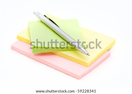 Thesilver pen lying on a colored notebook on a white background