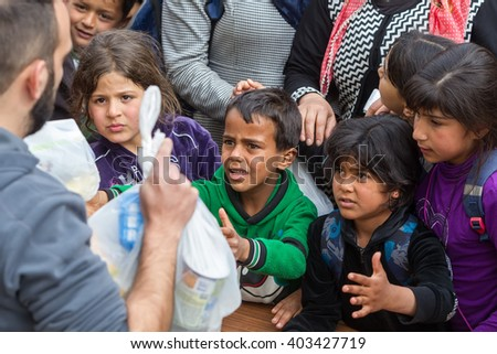 Thessaloniki, Greece - April 2, 2016: Refugees living in tents at the relocation center Diavata waiting in line to get food - stock photo