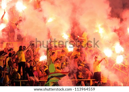THESSALONIKI, GREECE - AUGUST 5: Fans and supporters of ARIS team light flares in football match between Aris and Boca Juniors cheering for their team goals on August 5, 2009 in Thessaloniki, Greece. - stock photo