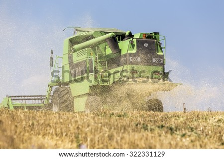 Thessaloniki, Greece - June 21, 2015: Combine harvester harvesting wheat on sunny summer day in Greece - stock photo