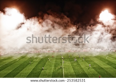 THESSALONIKI, GREECE NOVEMBER 9, 2014 : General view of the game with smoke over the pitch during the Greek Superleague match PAOK vs Panathinaikos. Digital filter has been added. - stock photo
