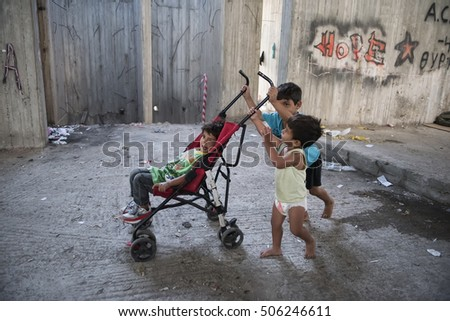 Thessaloniki, Greece - October 2, 2016. Refugee children from Afghanistan push a stroller, as they play inside an unfinished building site where they live with their families.