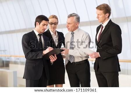 They all need an advice. Four business people discussing something while standing close to each other - stock photo